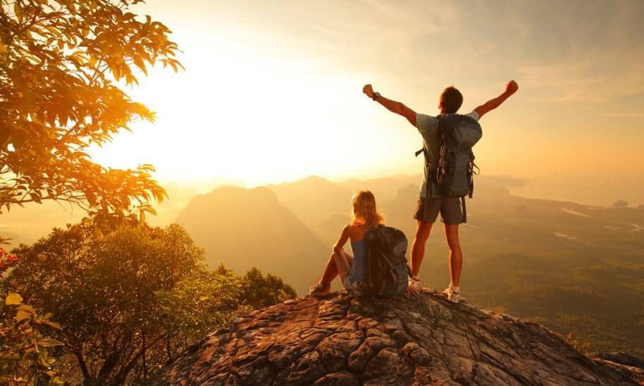 גבר עומד ואישה יושבת כאשר שניהם על פסגת הר בזריחה מסתכלים אל האופק