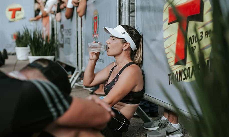 אישה יושבת בצד נשענת על הקיר שותה מים בעייפות