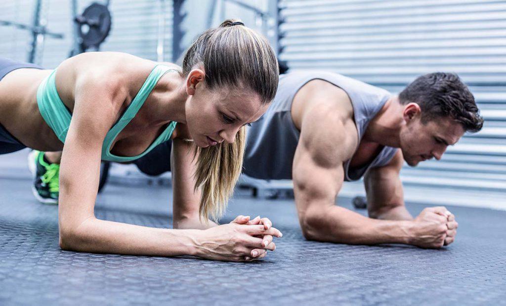 גבר ואישה עם מסת שריר גדולה עובדים על שרירי הבטן