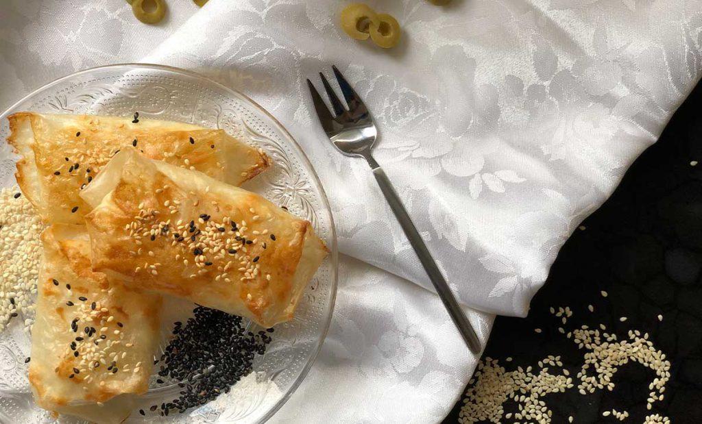 בורקס עשוי מדפי אורז על מפה לבנה ולידו חתיכות של זיתים, סומסום מפוזר ומזלג