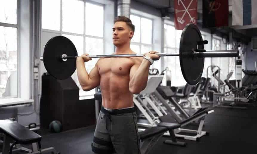 גבר צעיר וחטוב מחזיק מוט על הכתפיים מקדימה עם משקל בלי חולצה