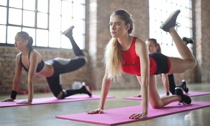 נשים בחדר כושר מבצעות תרגיל לישבן