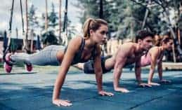 2 נשים וגבר במנח של שכיבת סמיכה עם רגליים באוויר בTRX