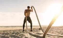 גבר מבצע אימון טבטה עם חבלים על חוף הים באמצע היום