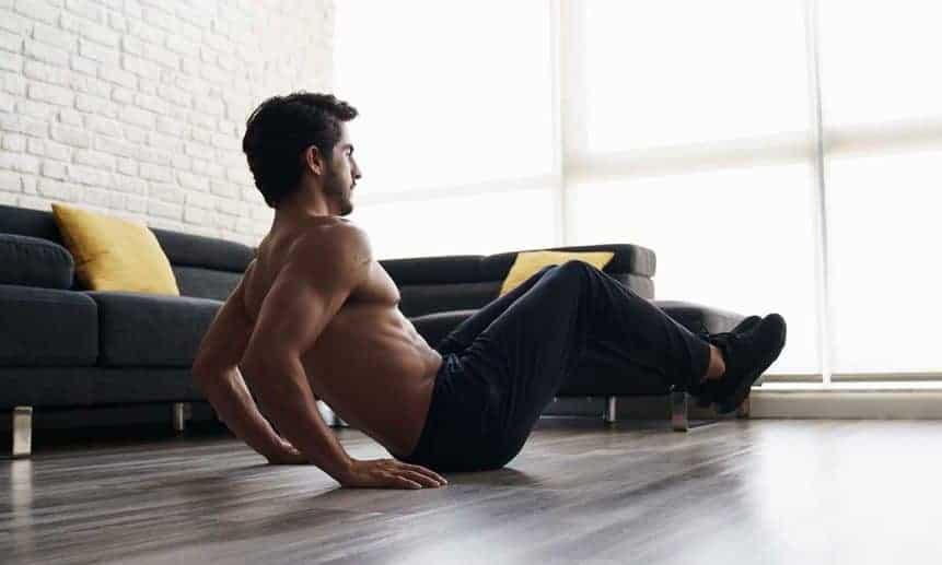 גבר בלי חולצה עם מכנס ארוך מתאמן בבית