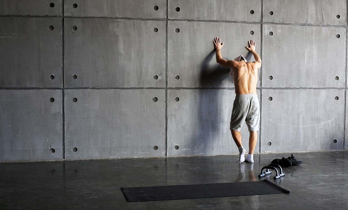גבר בלי חולצה בזמן מנוחה מהאימון מניח ידיים על הקיר בעייפות
