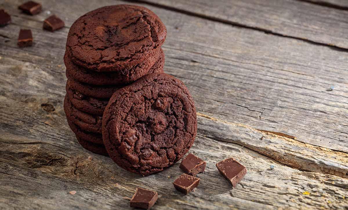 עוכיות שוקולד בערימה עם שוקולד ליד מונחות על שולחן עץ