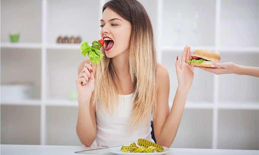 אישה אוכלת סלט עם יד אחת ודוחפת יד שמציעה לה המבורגר עם יד ימין