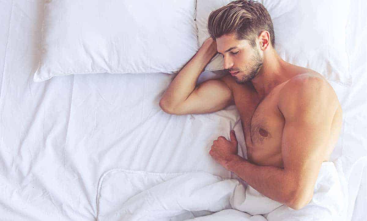 גבר שרירי ישן על מיטה לבנה