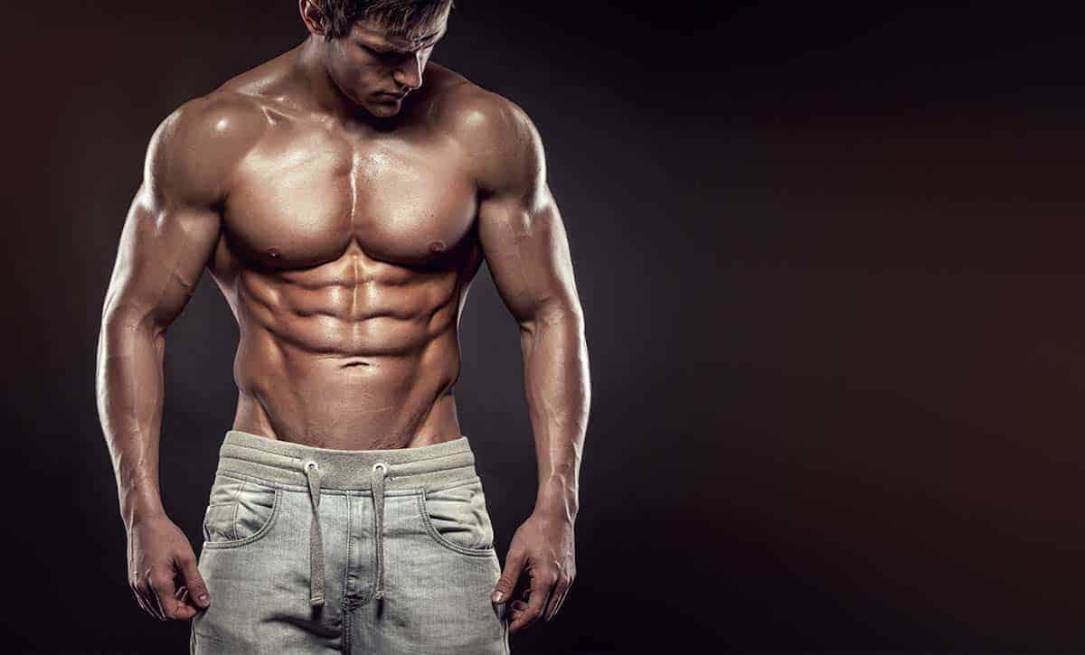 גבר חטוב ושרירי עומד בלי חולצה ומראה את ריבועים, וי קאט, ושרירי חזה וכתפיים